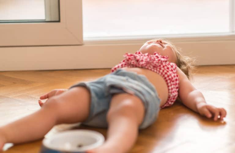 Barn i trotsåldern som lagt sig på golvet och skriker