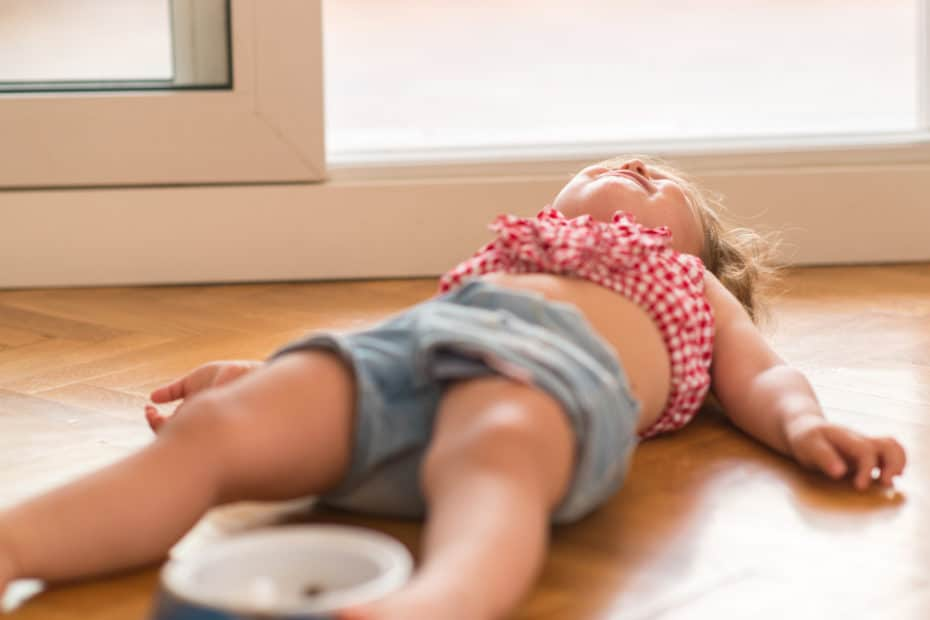 Child in a temper tantrum laying on the floor and screaming