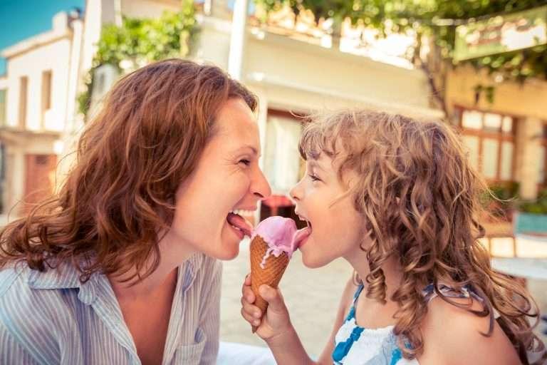 Barn och mamma äter glass med socker tillsammans