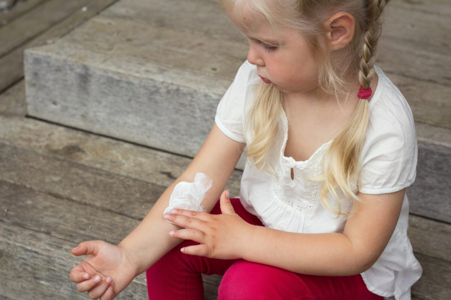 Child applying cream on her inner forearm