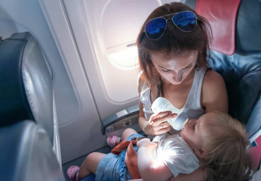 A mother travels abroad with babies and feeds her baby with a baby bottle in an airplane