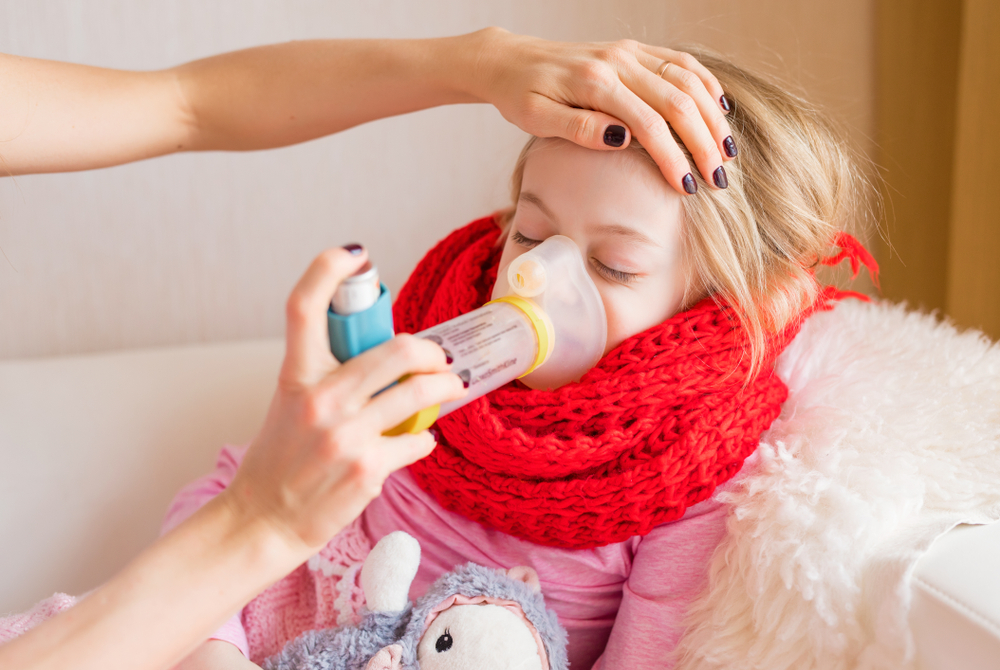 Child receiving asthma treatment with inhaler attached to a spacer and mask.