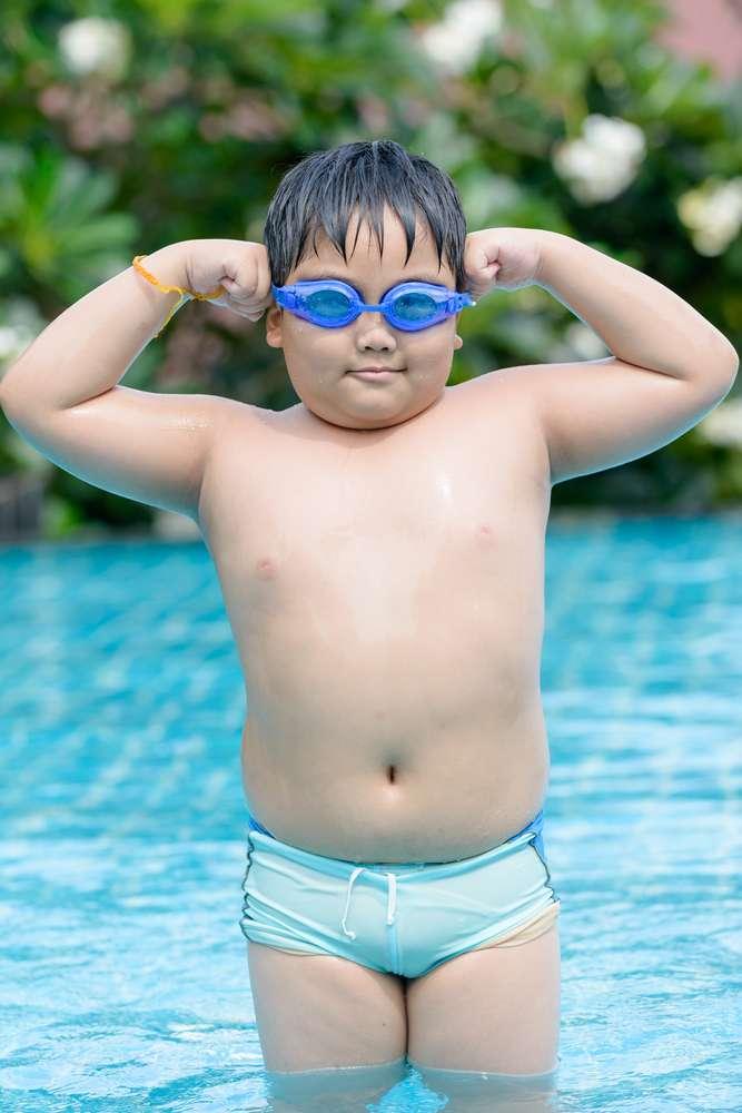 En glad pojke med övervikt som badar