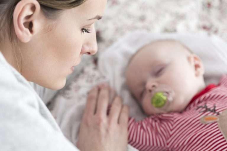 Mamma tittar på sovande bebis och undrar om hon ska sluta amma